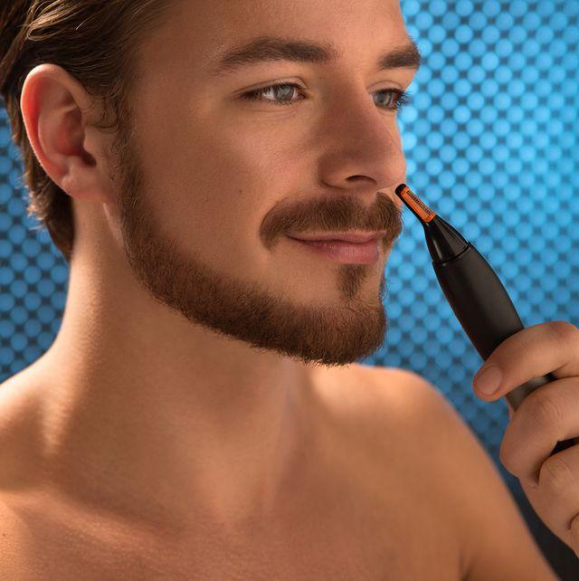 hombre usando un cortapelos de nariz
