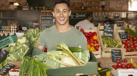 young man holding tray of fresh vegetables