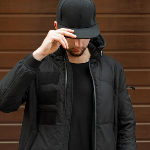 young man in a black fashionable baseball cap and a winter warm jacket posing on the street
