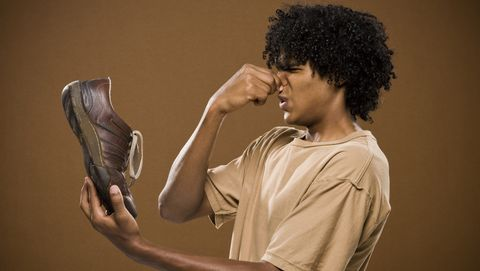 young man in a brown shirt holding a shoe and his nose