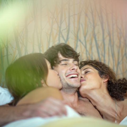 Young man in bed with two young women