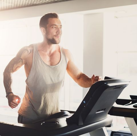 young man in gym run on treadmill
