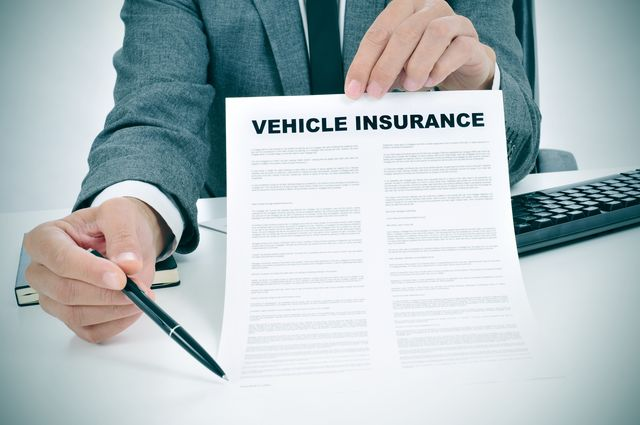 young man in suit showing a vehicle insurance policy