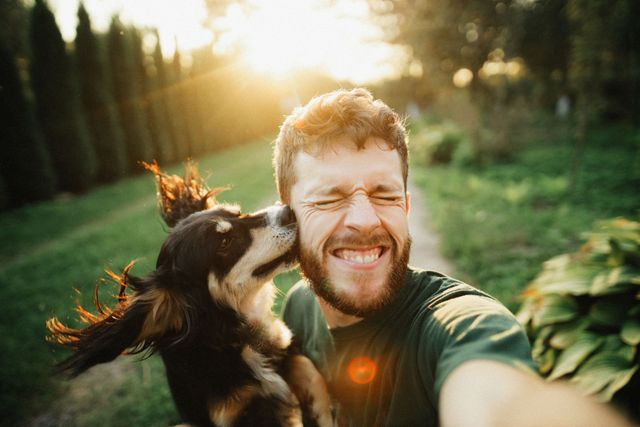 young man is playing with a dog and do selfie