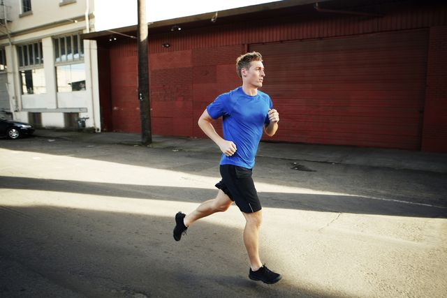 young man jogging on street in city