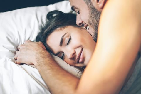 Young Man Kissing Girlfriend On Bed