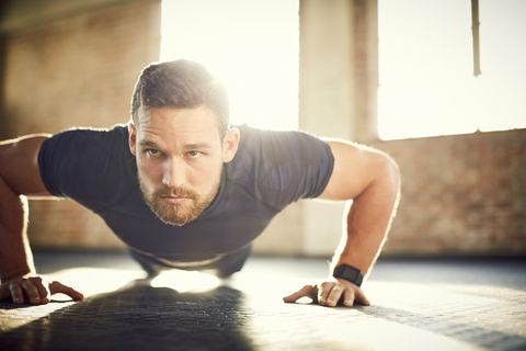 Young man looking away while doing push-ups in gym