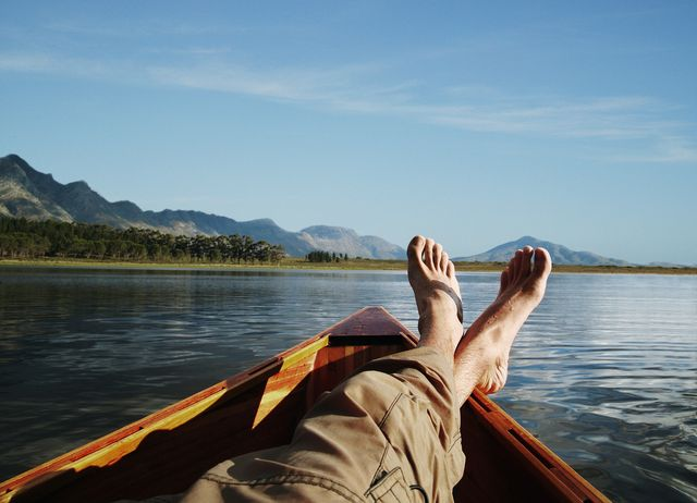 young man lying in boat on lake, low section