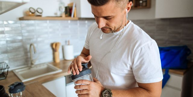 young man making protein shake before training