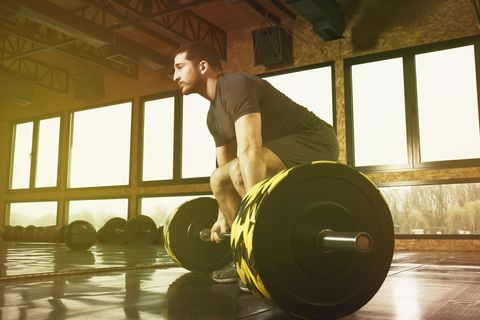 young man on cross training lifting weights in gym
