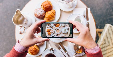 Young man photographing French breakfast with croissants on the table in sidewalk cafe with smartphone, Paris, France