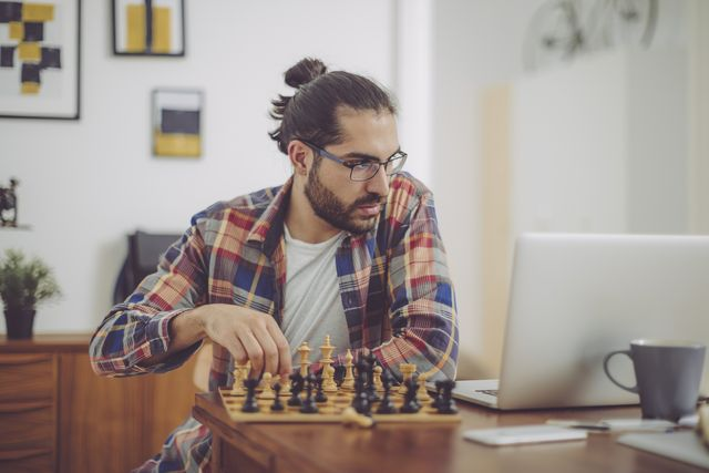 young man playing chess at home