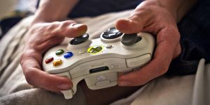 A young man plays a video game with his hands on a Xbox controller from the American company Microsoft. Denmark 2012.
