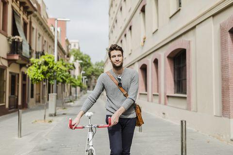 Jeune homme poussant son vélo