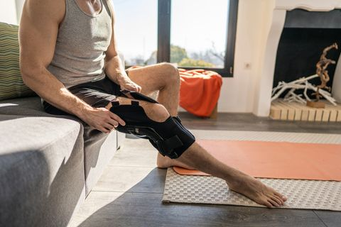 young man putting on knee bandage fixator before exercising