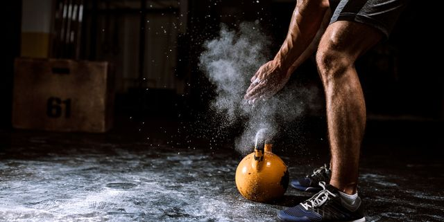 young man putting on sports chalk for lifting barbell