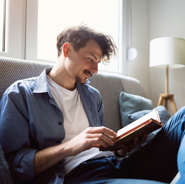 young man reading a book at home