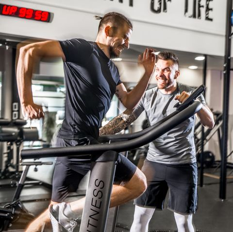 Young Man Running on Treadmill while Fitness Instructor Motivates Him