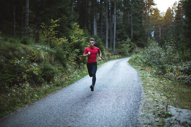 young man runs in pine forest at sunrise