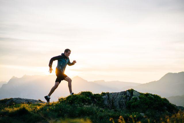 young man runs on mountain ridge at sunrise