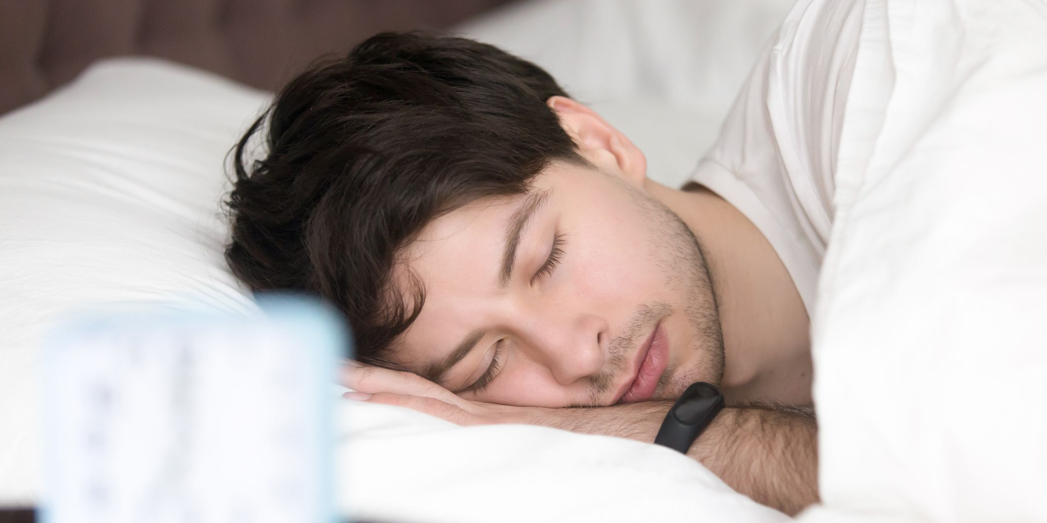 Young man sleeping next to alarm clock wearing smart wristband