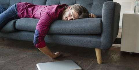 Young man sleeping on sofa with laptop