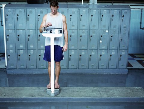 Young man stading on scale in locker room