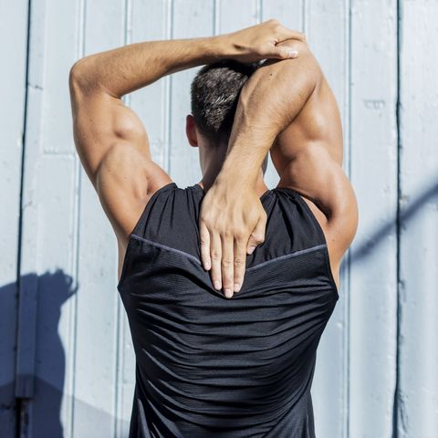 young man stretching against a blue wall after a workout
