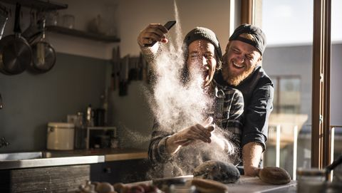 Young man taking pictures of his friend, cooking in the kitchen