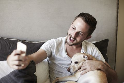 Young man taking smartphone selfie with dog on bed