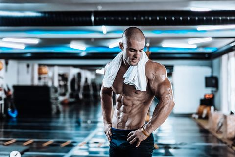 Young man tired after training showing his abdominal muscles