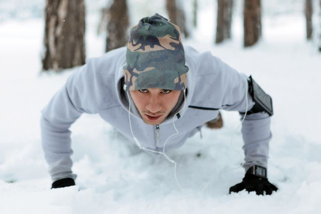 young man training in snow doing pushups