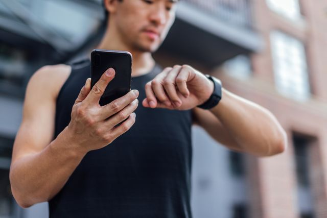 young man using fitness app on smart phone and smart watch for tracking workout