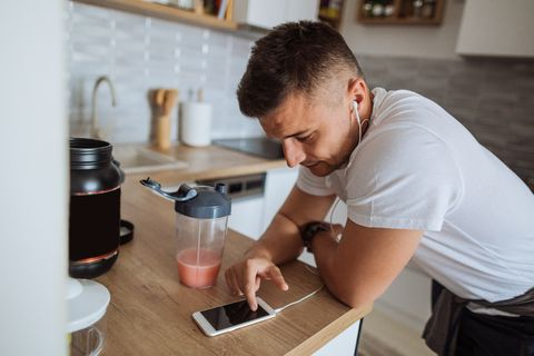 Young man using running app on smartphone to track progress