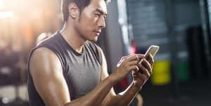 Young man using smart phone in gym