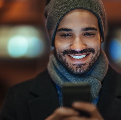 Young man using smartphone on city street at night