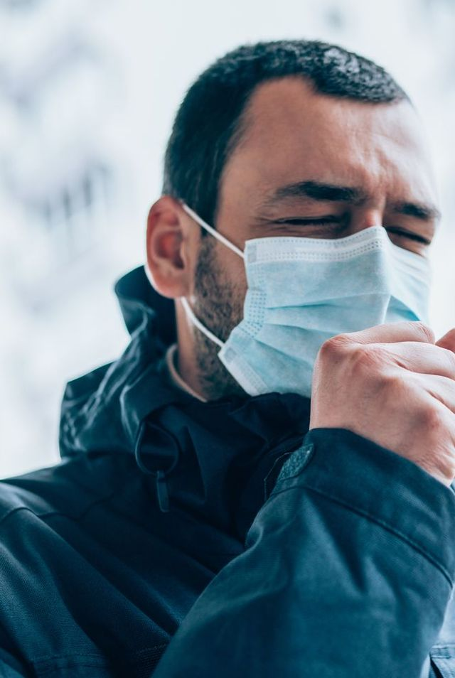 young man wear face mask and coughing outdoors