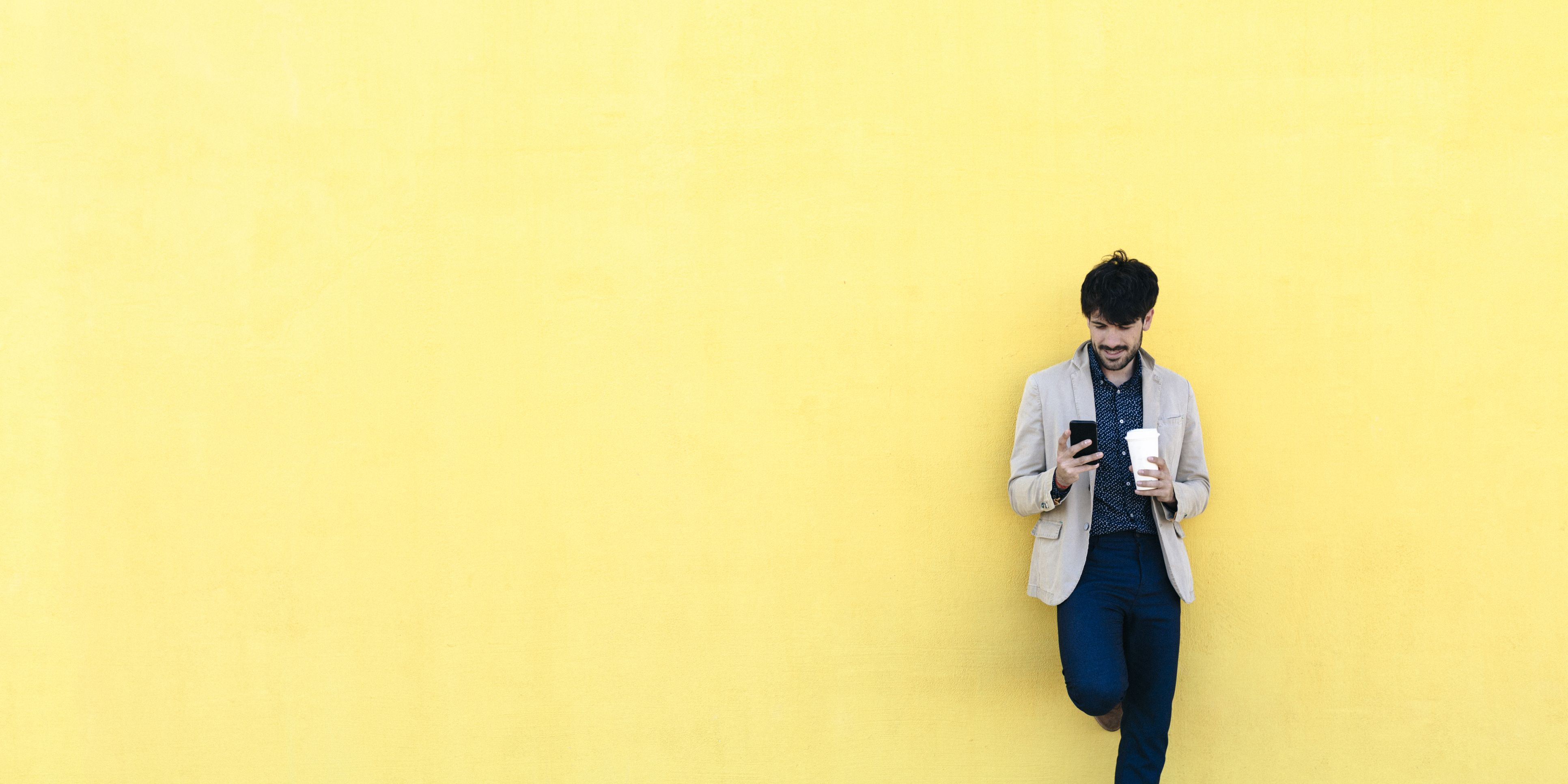 Young man with coffee to go checking the cell phone in front of yellow wall