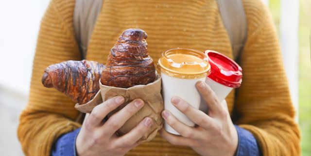 young man with croissant and coffee to go