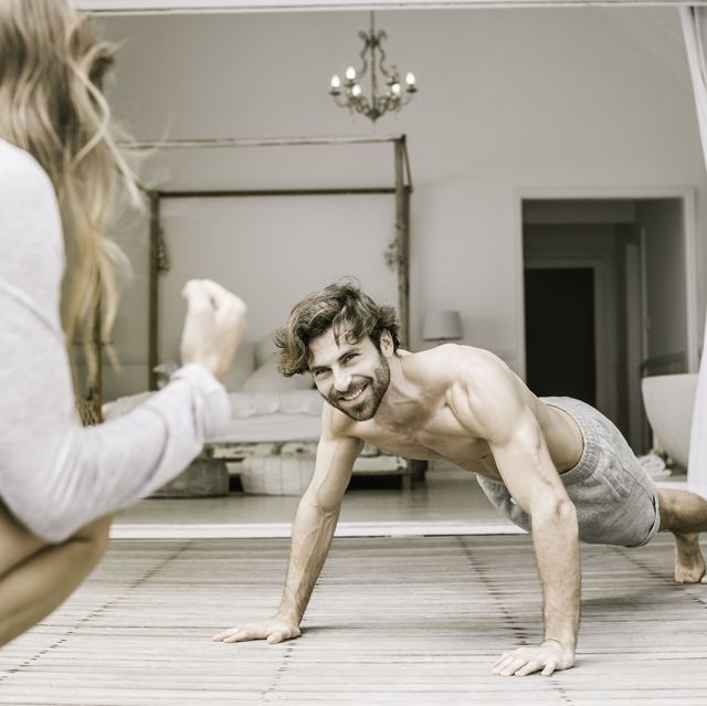 Young man with girlfriend doing press ups in bedroom