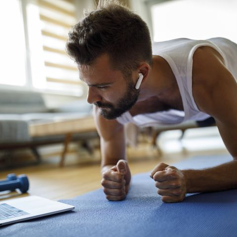 young man with headphones using laptop for exercising at home