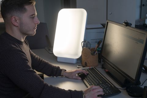 young man working at the office with light therapy lamp