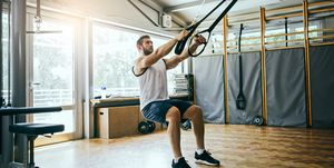 Young man workout with TRX Suspension