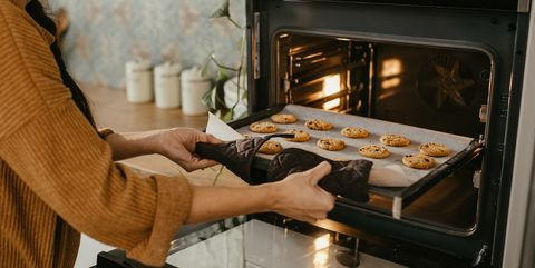 young mother putting a tray full of cookies in the oven