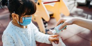 Young mother squeezing hand sanitizer onto little daughter's hand in the playground to prevent the spread of viruses