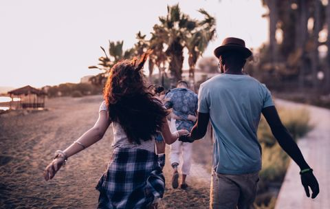 Young multi-ethnic couples walking on tropical island beach at sunset