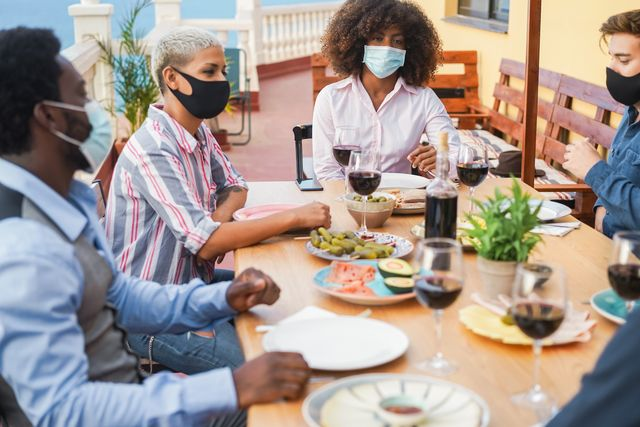 young people eating and drinking together while wearing face protective masks