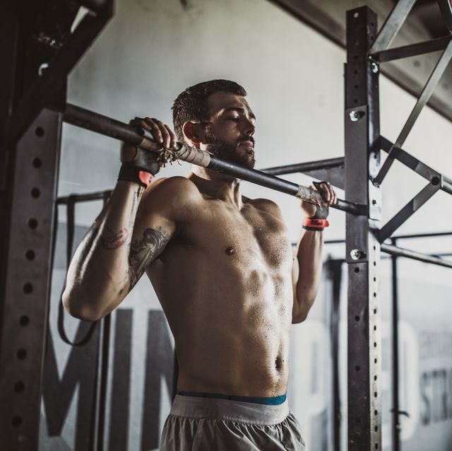 Young muscular build athlete exercising pull-ups in a gym.