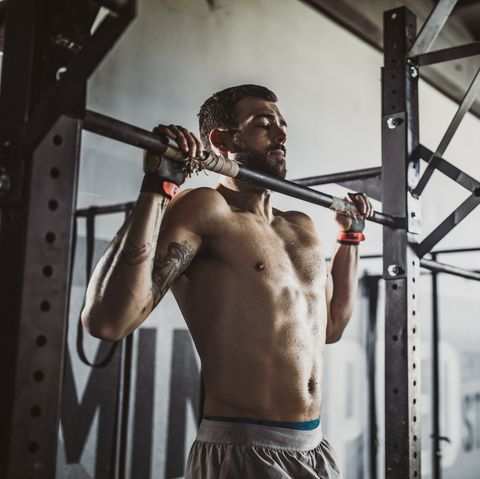 young muscular build athlete exercising pullups in a gym