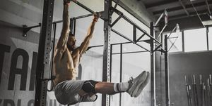 Young muscular build athlete exercising strength in a gym.